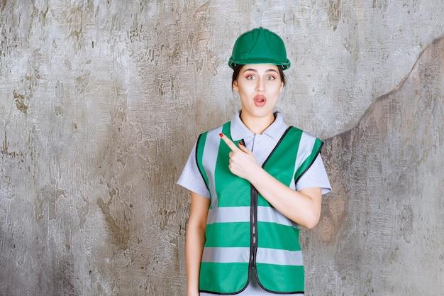 Ingegnere donna in uniforme verde e casco che mostra il lato sinistro con emozioni