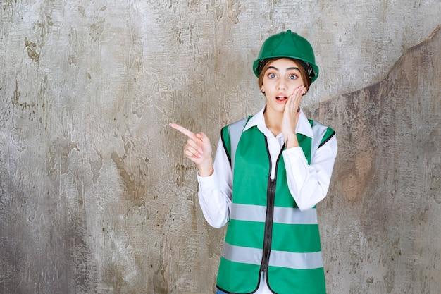 Ingegnere donna in uniforme verde e casco in piedi sul muro di cemento e rivolto verso il lato sinistro