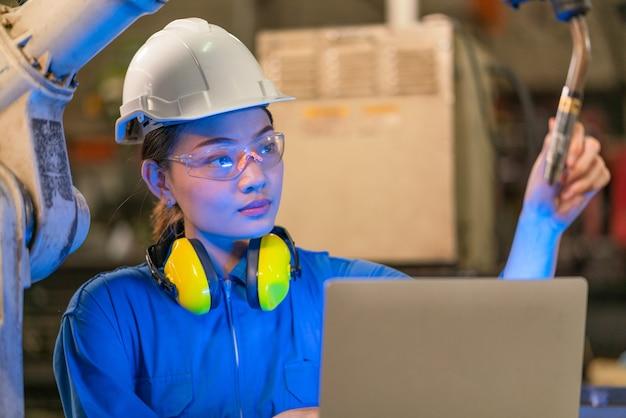 Ingegnere femminile che programma una macchina a braccio robotico per la saldatura del sistema con il controllo del computer portatile in una fabbrica industriale