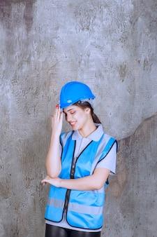 Ingegnere donna che indossa casco blu e attrezzatura e tiene la testa mentre è stanca o ha mal di testa.