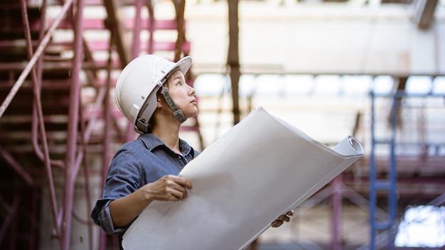 Casco di sicurezza d'uso dell'ingegnere femminile mentre tenendo il modello sulle sue mani.