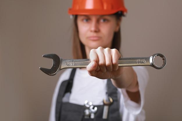 Operaio ingegnere femminile in un casco uniforme e di sicurezza con strumento, chiave in mano e mostrando a porte chiuse.