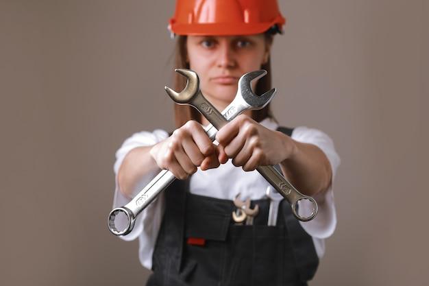 Operaio ingegnere femminile in un casco uniforme e di sicurezza con due chiavi a croce in mano e mostrando a porte chiuse.