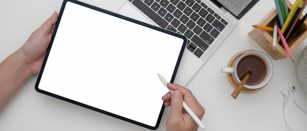 Imprenditore femminile che per mezzo della compressa dello schermo in bianco mentre lavorando con il computer portatile sulla scrivania bianca