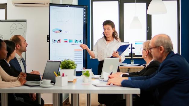 Presentatrice di coach leader esecutivo femminile che dà presentazione finanziaria nella moderna sala riunioni dell'ufficio per il gruppo di dipendenti aziendali, mentore dell'altoparlante che spiega la formazione del team di professionisti al seminario aziendale