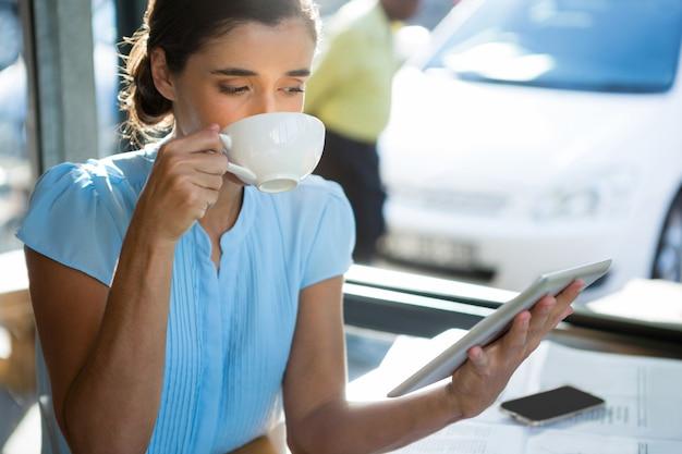 Dirigente femminile che utilizza la compressa digitale mentre beve il caffè