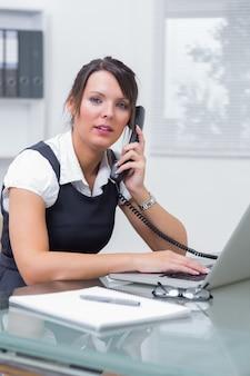 Esecutivo femminile con il computer portatile che utilizza il telefono di rete fissa all'ufficio