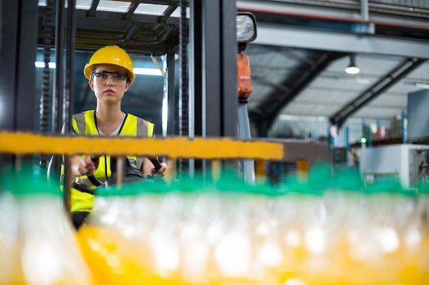 Operaio femminile che guida carrello elevatore in fabbrica