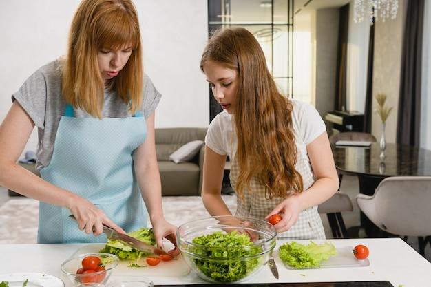 Famiglia femminile che fa insieme insalata a casa home