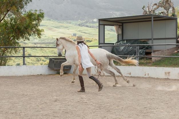Coltivatore femminile con il suo cavallo al ranch