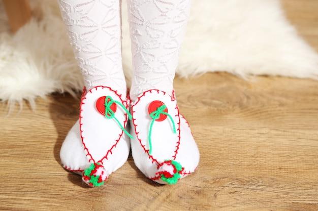 Piedi femminili in scarpe di natale decorative