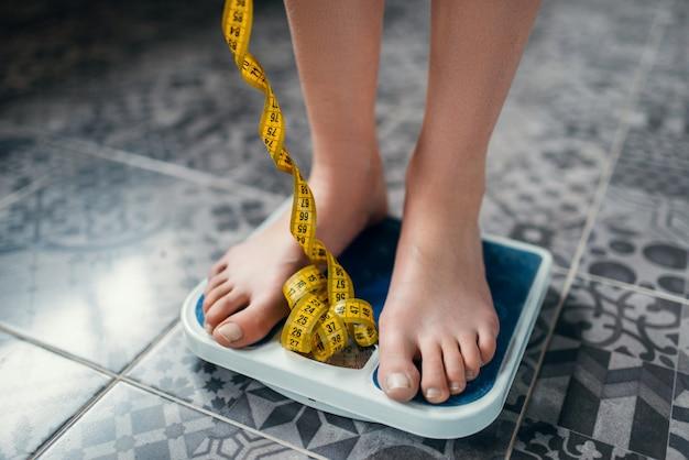Piedi femminili sul primo piano delle scale, nastro di misurazione. concetto di bruciare calorie o grassi. perdita di peso, dieta difficile