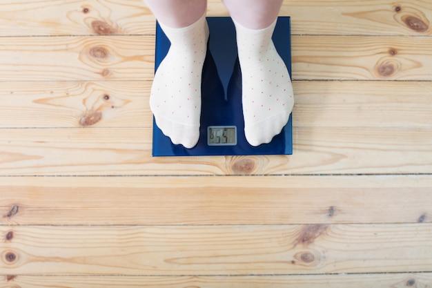 Piedi femminili in calzini sulla bilancia da pavimento