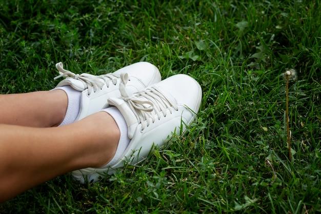 Piedi femminili in scarpe da ginnastica bianche sull'erba verde. attività e relax durante la bella stagione.