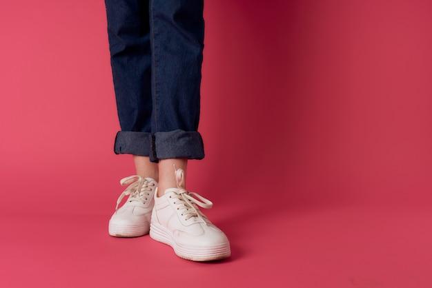 Piedi femminili scarpe da ginnastica bianche street fashion muro rosa.