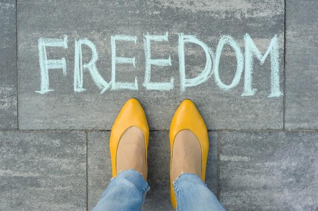 Piedi femminili con libertà di testo scritta sul marciapiede grigio