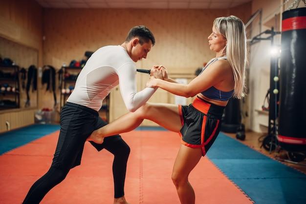 Combattente femminile che si nasconde da un colpo di coltello in allenamento di autodifesa con personal trainer maschile
