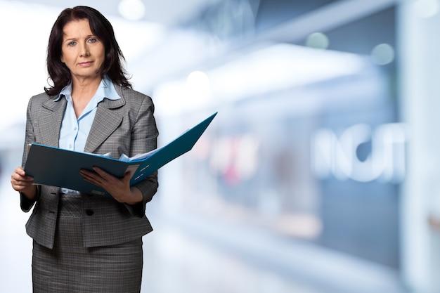 Consulente finanziario femminile che tiene cartella sullo sfondo