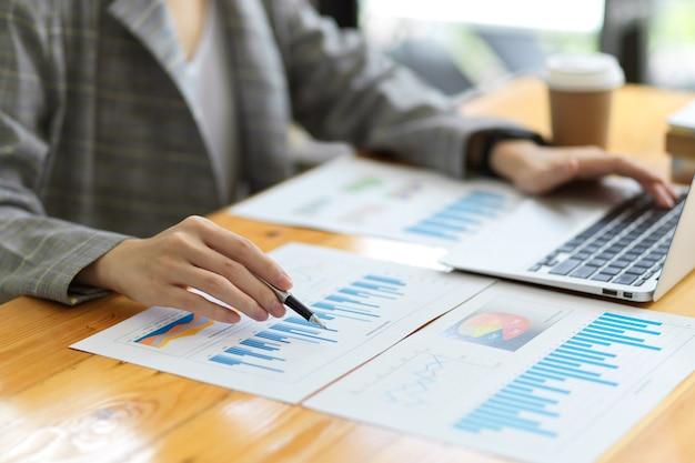 Funzionario finanziario femminile che lavora in ufficio, lavora su un computer portatile, analizza i fondi finanziari dell'azienda con rapporti finanziari sulla scrivania