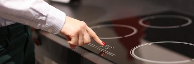 Dito femminile preme il pulsante sul touch stufa elettrica vendita di elettrodomestici koncetp