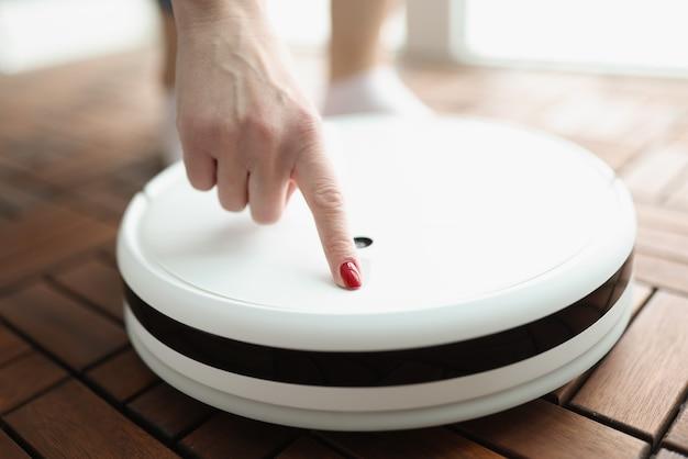 Il dito femminile preme il pulsante di accensione sull'aspirapolvere robotico bianco