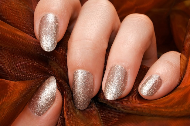 Le dita femminili con smalto per unghie d'argento tengono il tessuto arancione.
