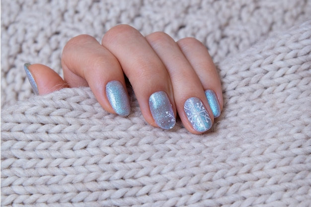 Dita femminili con manicure invernale sul maglione