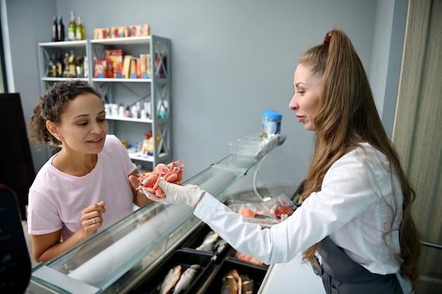 Pescivendolo femminile che tiene gamberetti raffreddati nelle sue mani e sorride carino, vendendo i frutti di mare al cliente.