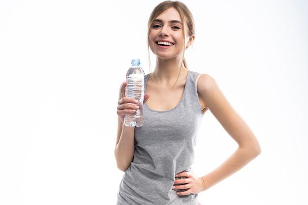 Modello di fitness femminile che tiene una bottiglia d'acqua in un ambiente di studio bianco