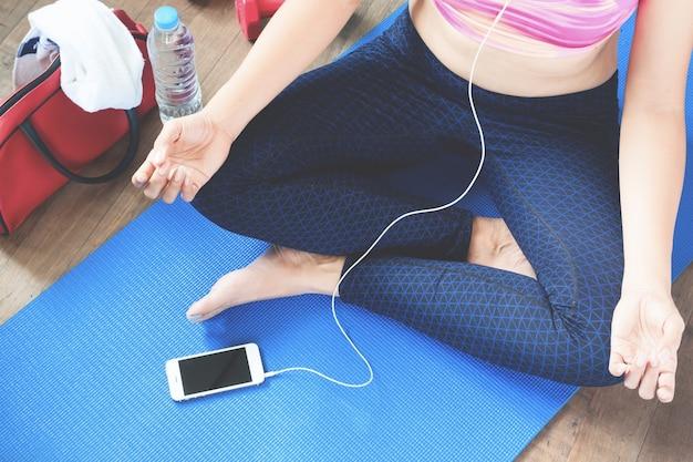 Concetto femminile fitness e yoga excercise con copia spazio, musica femminile di ascolto da smartphone aafter allenamento