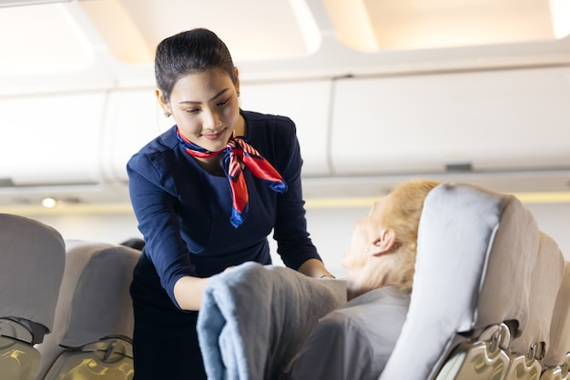 Un'assistente di volo donna ha vestito un passeggero anziano che dorme sul sedile del passeggero