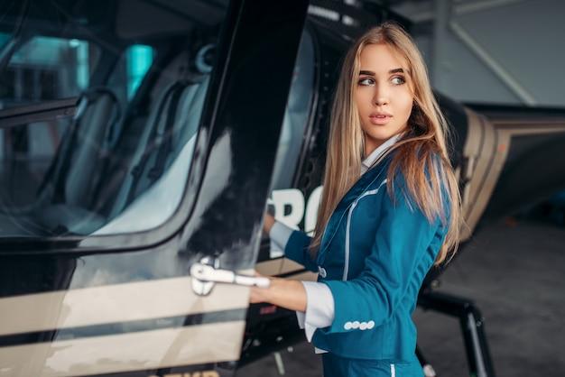 L'assistente di volo femminile posa contro l'elicottero