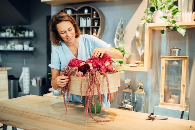 Fiorista femmina decora frsh bouquet di fiori in negozio. artista floreale che fa la composizione sul posto di lavoro. servizio di fiorai