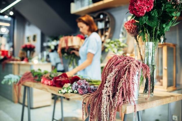 Fiorista femminile che fa la disposizione dei fiori sul tavolo in negozio. l'artista floreale decora il bouquet sul posto di lavoro