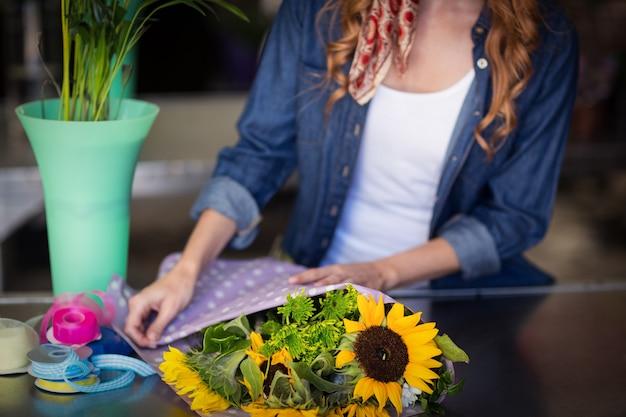 Fiorista femminile che avvolge il mazzo del fiore