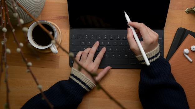 Free lance femminili che per mezzo della compressa digitale, della tazza di caffè, del libro di programma e della decorazione sulla scrivania del ministero degli interni