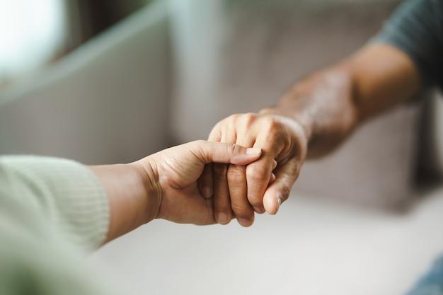 Amica o famiglia che si tiene per mano durante il rallegramento dell'uomo depresso mentale, lo psicologo fornisce aiuto mentale al paziente ptsd concetto di salute mentale