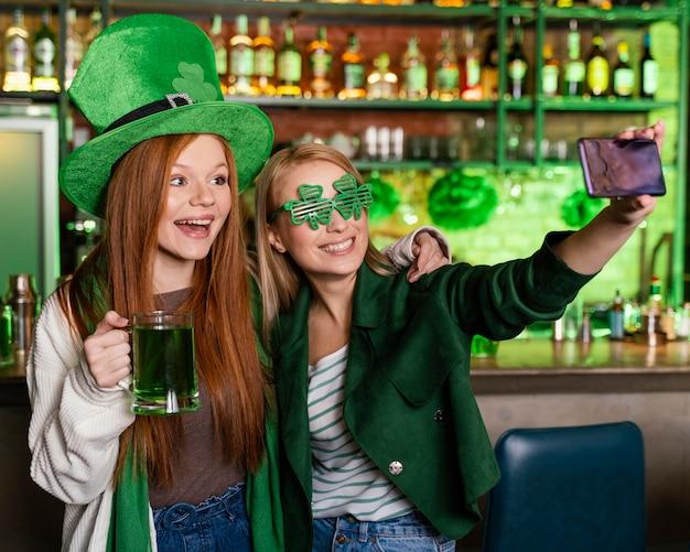 Amici femminili che celebrano st. patrick's day al bar e prendendo selfie insieme