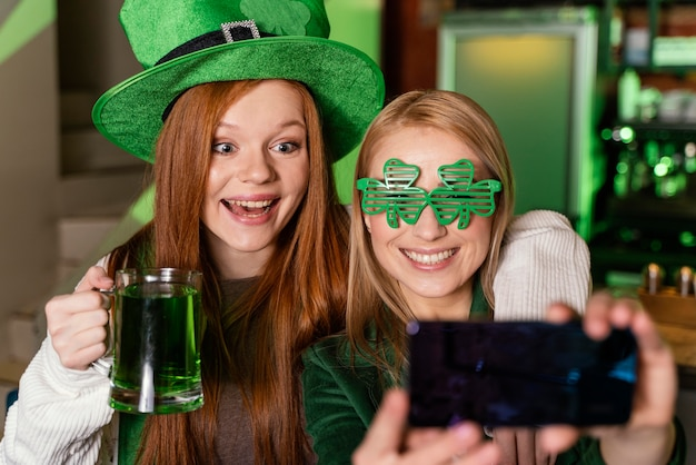 Amici femminili che celebrano st. patrick's day al bar e prendendo selfie con bevande