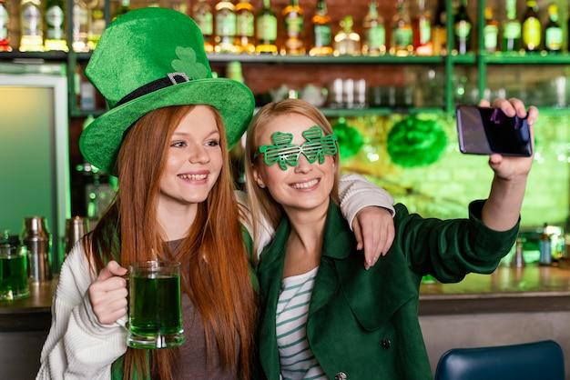 Amici femminili che celebrano st. patrick's day al bar e prendendo selfie