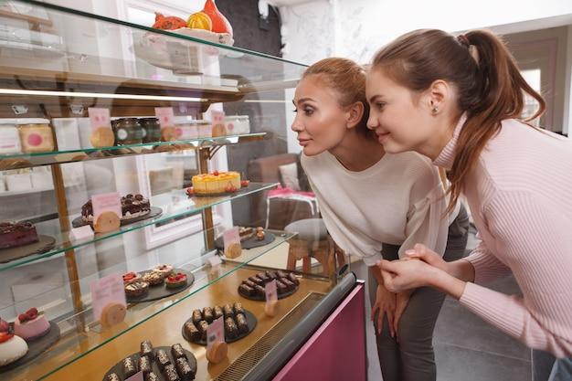 Amici femminili che scelgono i dessert dall'esposizione al dettaglio in pasticceria