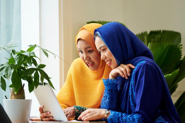 Amici femminili che discutono informazioni sul computer tablet