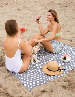 Amici femminili che mangiano anguria in spiaggia