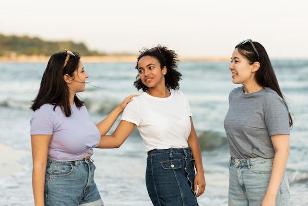 Amici femminili che hanno divertimento insieme sulla spiaggia