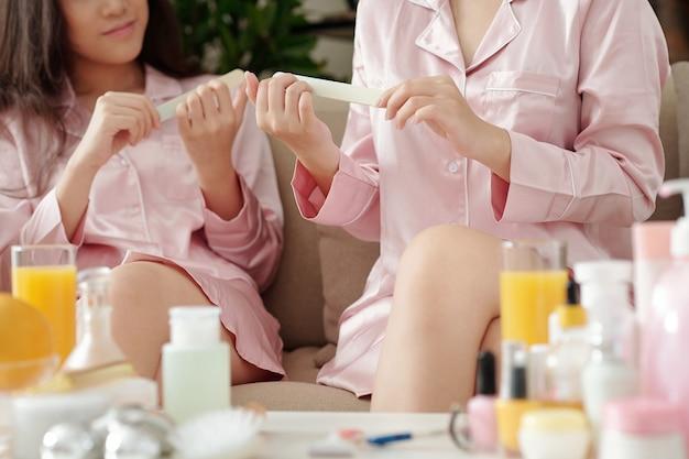 Amiche in pigiama di seta trascorrono la serata insieme limando le unghie e parlando
