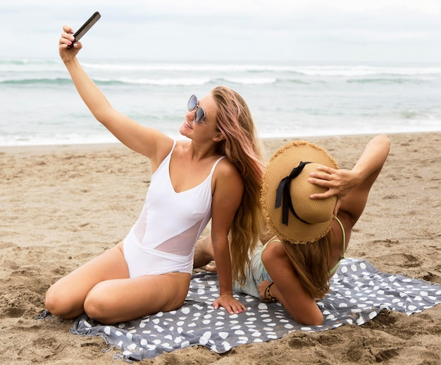 Amici femminili che prendono selfie sulla spiaggia insieme