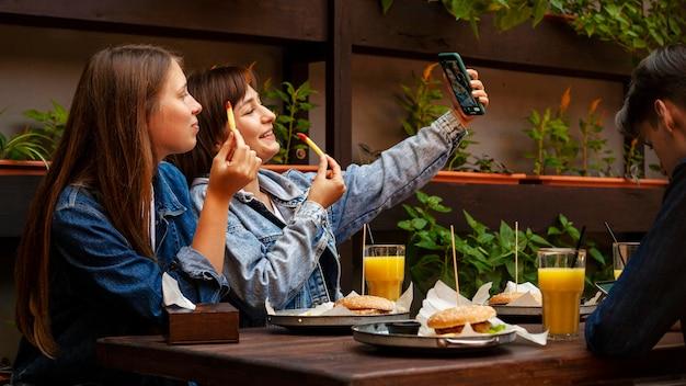 Amici femminili che prendono selfie pur avendo patatine fritte