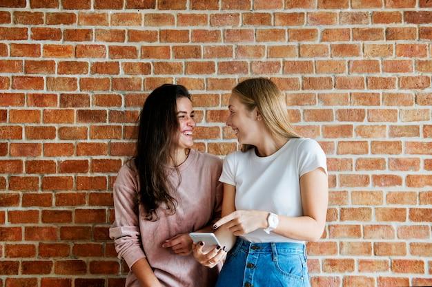 Amici femminili che usando insieme uno smartphone