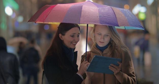 Amiche che usano il touch pad in una serata piovosa in città