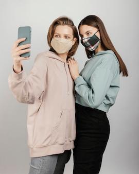 Amici femminili che indossano maschere e prendendo selfie